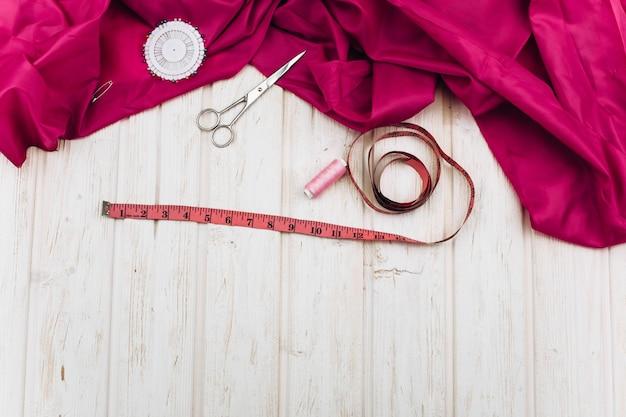 어두운 분홍색 천, 가위, 바늘, 단추 및 실 나무 테이블에 누워