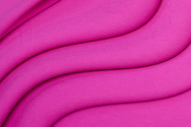 濃いピンクの綿生地の背景、上面図。