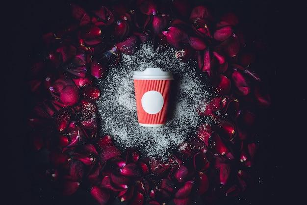 Темно-розовые лепестки лежат вокруг красной бумажной чашки