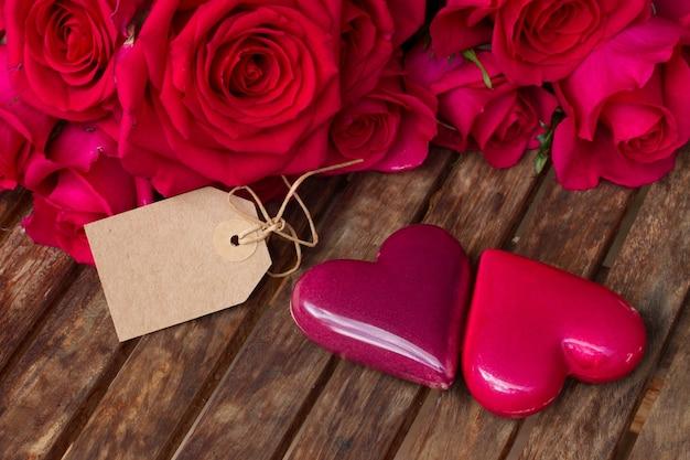 두 개의 하트와 나무 테이블에 빈 종이 태그와 어두운 분홍색 장미