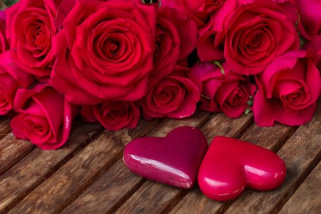 나무 테이블에 두 마음으로 어두운 핑크 장미