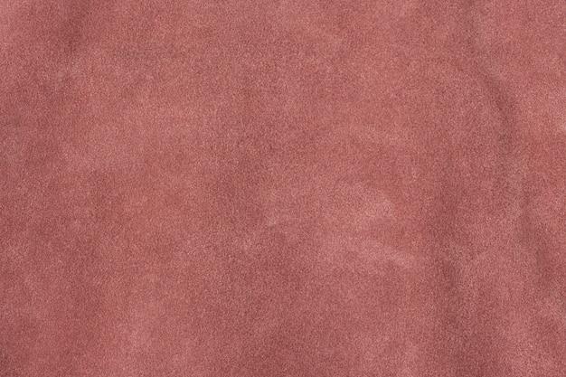 Темно-розовый текстурированный фон поверхности замши