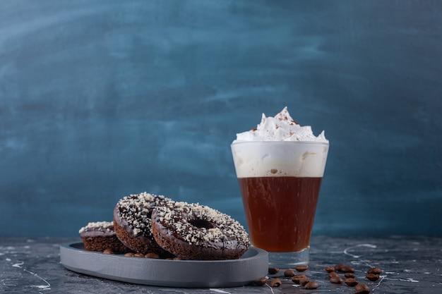 Piatto scuro di ciambelle al cioccolato con granelli di cocco e delizioso caffè su fondo di marmo.