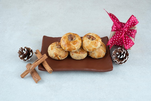 A dark plate of cookies with christmas small present and pinecones .