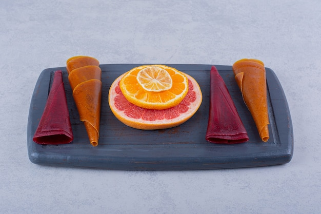 Dark plate of delicious dry fruit pulps and grapefruit on stone table.