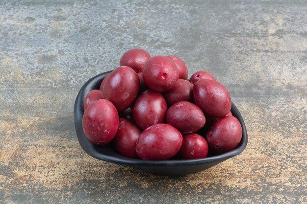 Un piatto scuro di deliziosi frutti su sfondo bianco. foto di alta qualità