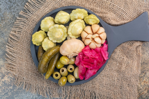 A dark plate full of cabbage and pickled cucumbers . high quality photo