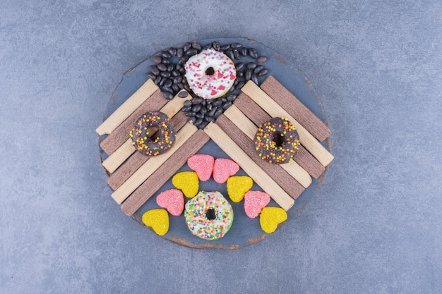 A dark plate full of donuts and heart shaped jelly candies
