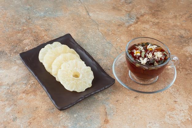 Un piatto scuro pieno di ananas sano essiccato e tazza di tè