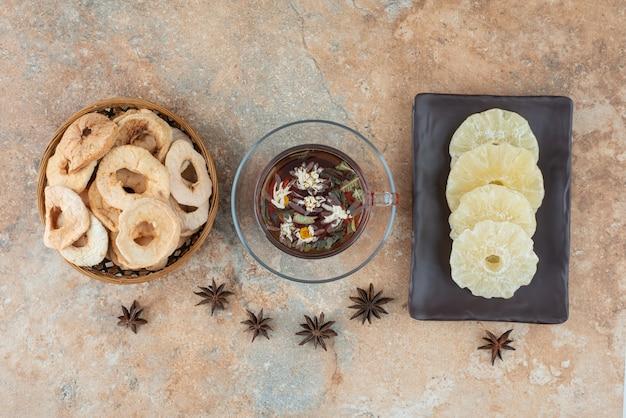Un piatto scuro pieno di ananas essiccato e una tazza di tisana
