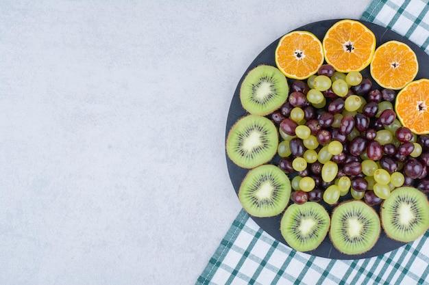 Un piatto scuro pieno di uva, kiwi e arancia sulla tovaglia. foto di alta qualità