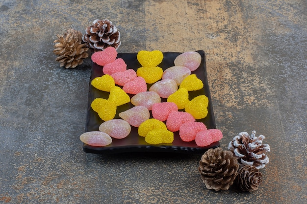 A dark plate full of heart shaped sugary jelly candies with pinecones. high quality photo