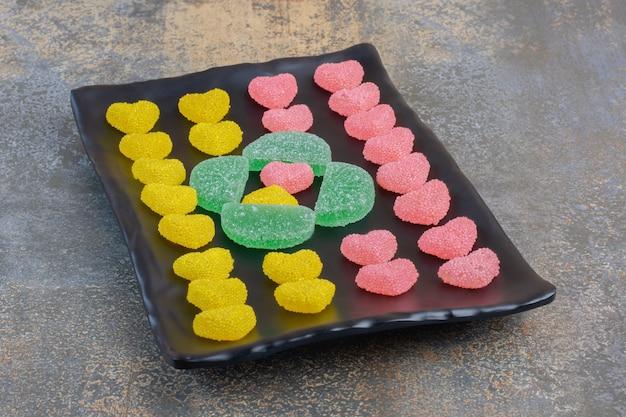 Un piatto scuro pieno di caramelle di gelatina zuccherina a forma di cuore con pigne. foto di alta qualità