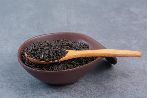 Un piatto scuro pieno di infuso con cucchiaio di legno.