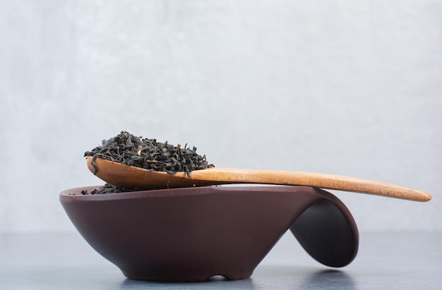 A dark plate full of infusion with wooden spoon