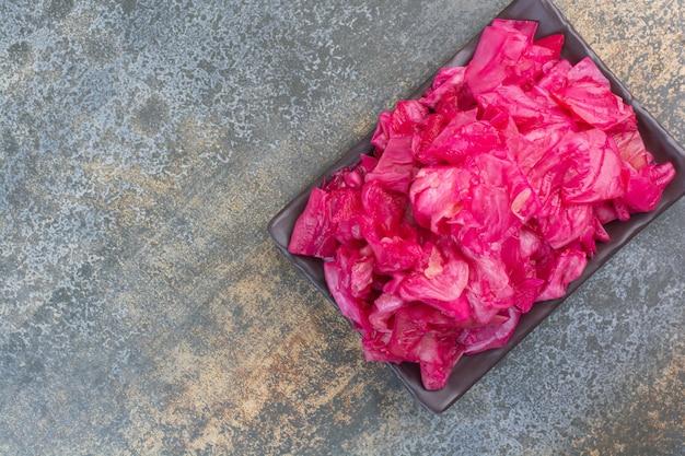 Un piatto scuro pieno di cavolo salato rosso su sfondo marmo. foto di alta qualità