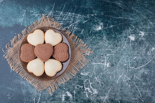 Dark plate of heart shaped cookies placed on marble background .