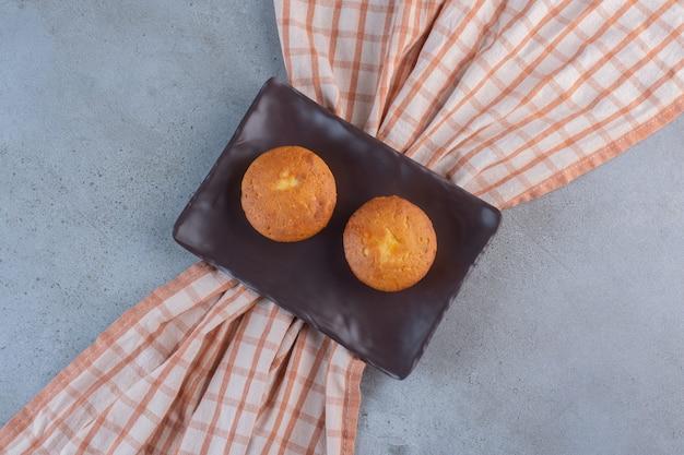 Piatto scuro di mini torte dolci su fondo di pietra.