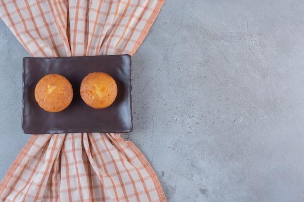 Piatto scuro di mini torte dolci su pietra.