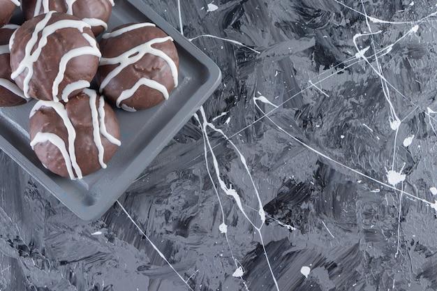 대리석 테이블에 신진 장미와 초콜릿 볼의 어두운 접시.