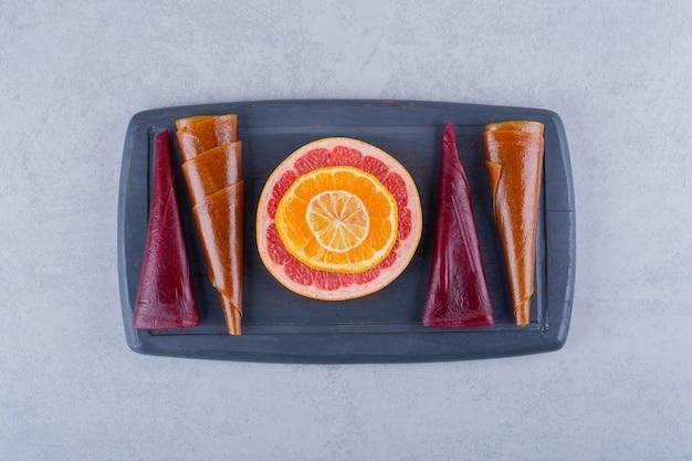Темная тарелка вкусной мякоти сухих фруктов и грейпфрута на каменном столе.