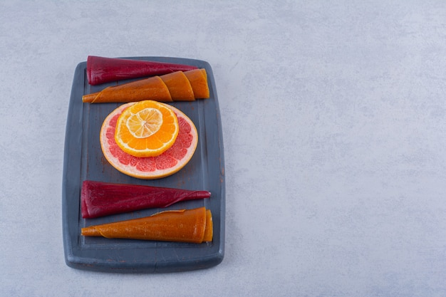 Темная тарелка вкусной мякоти сухих фруктов и грейпфрута на камне.
