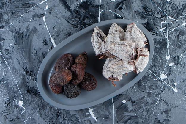 大理石の表面に乾燥したおいしい柿と日付の暗いプレート