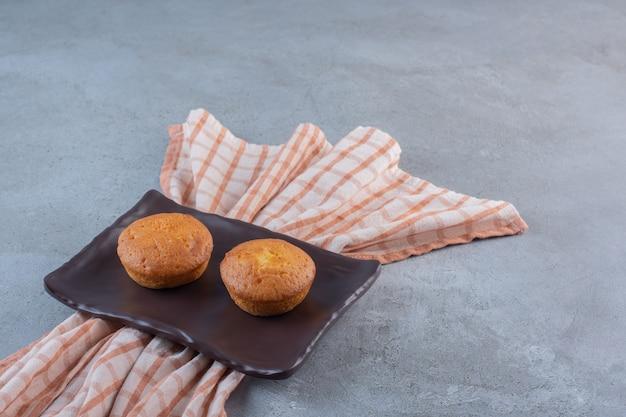 石のテーブルの上のミニ甘いケーキの暗いプレート。