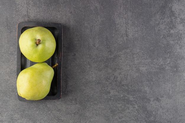 Темная тарелка вкусных зеленых груш на каменной поверхности