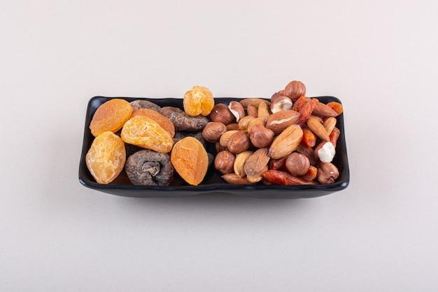 Темная пластина различных органических орехов на белой поверхности. фото высокого качества