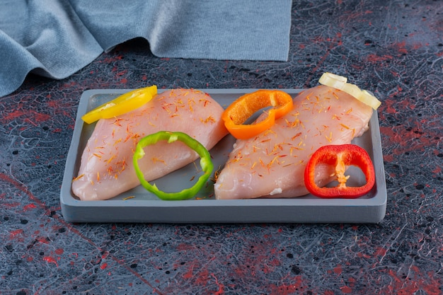 Dark plate of raw chicken breast with chopped peppers on marble background.