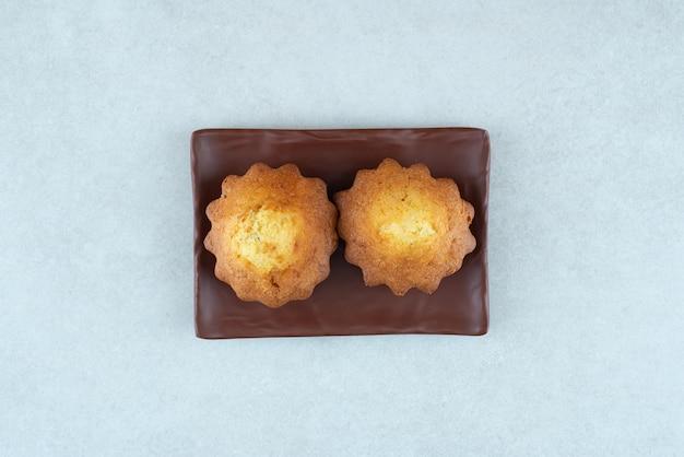 Un piatto scuro di due deliziosi cupcakes sul tavolo bianco.