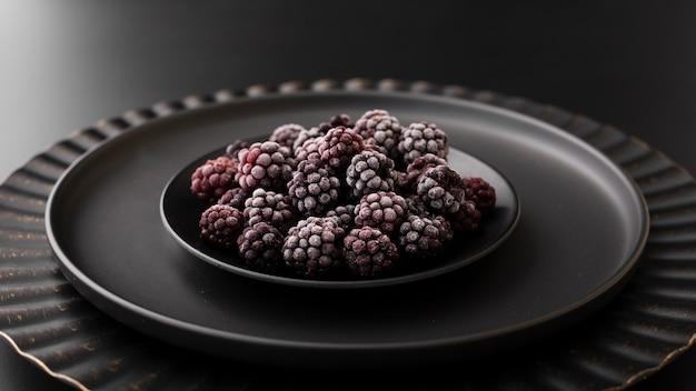 Dark plate with blackberries on a dark table