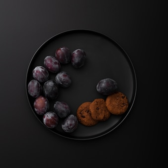 Dark plate with cookies and plums on a dark background