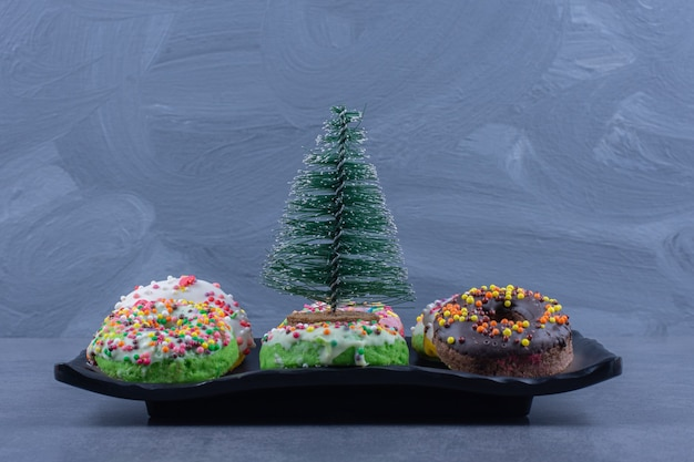A dark plate with delicious donuts and small christmas tree
