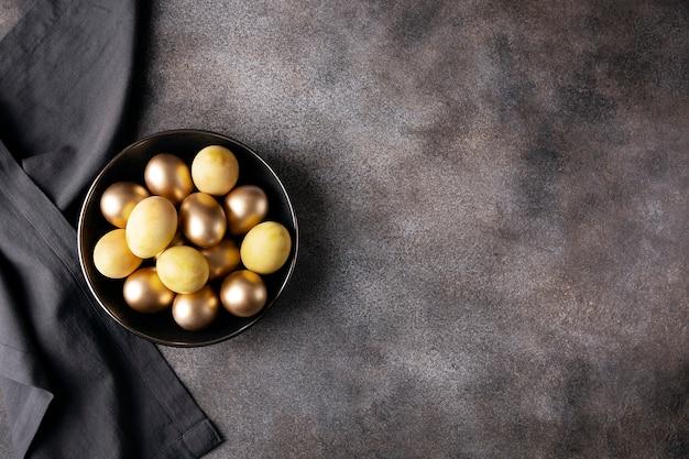 어두운 콘크리트에 황금 부활절 달걀과 어두운 접시