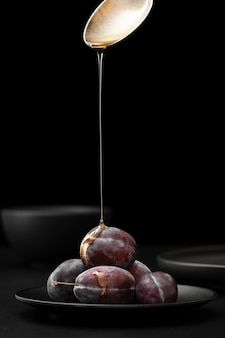 Dark plate with plums on a dark background