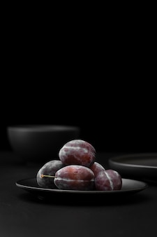 Dark plate with plums on a dark table