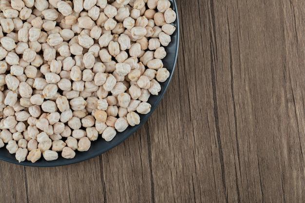 Un piatto scuro con piselli bianchi non preparati su un tavolo di legno