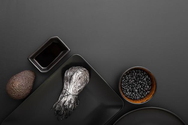 Темные тарелки с фасолью и макаронами на темном фоне