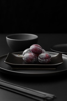 Dark plates with plums on a dark table