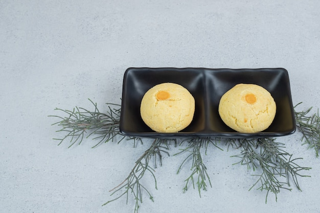 Piatti scuri con due biscotti dolci rotondi su superficie bianca