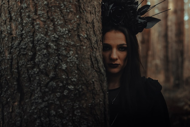 Dark portrait of a frightening witch in black costume in the woods