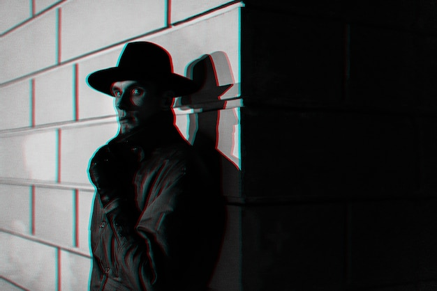 Dark portrait of a man in a raincoat with a hat at night on the street. black and white with 3d glitch virtual reality effect
