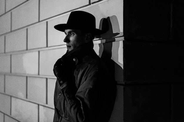 Dark portrait of a man in a raincoat with a hat at night on the street in a crime noir style