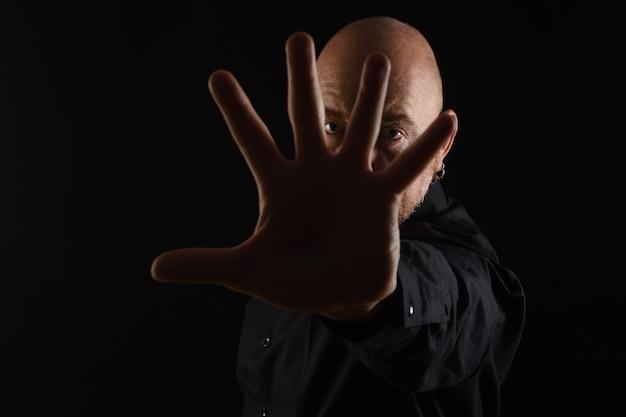 Dark portrait of a man with open palm on black bakcground