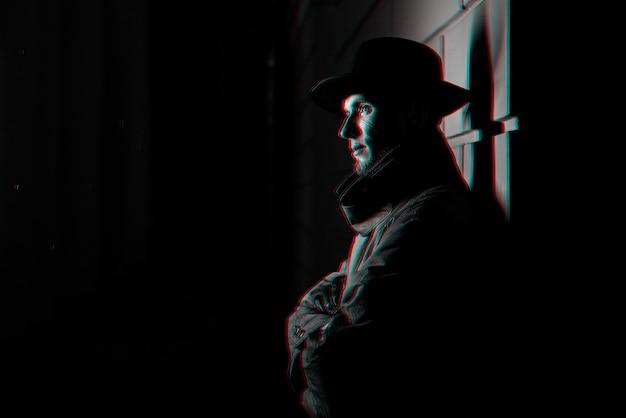 路上で夜に帽子をかぶったレインコートを着た男の暗い肖像画。 3dグリッチバーチャルリアリティ効果のある白黒