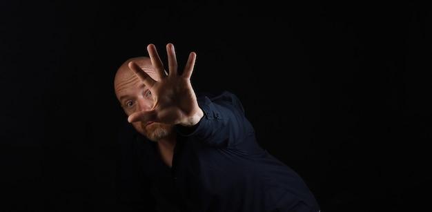 黒のbakcgroundに一時停止の標識を伸ばした手を持つ男の暗い肖像画