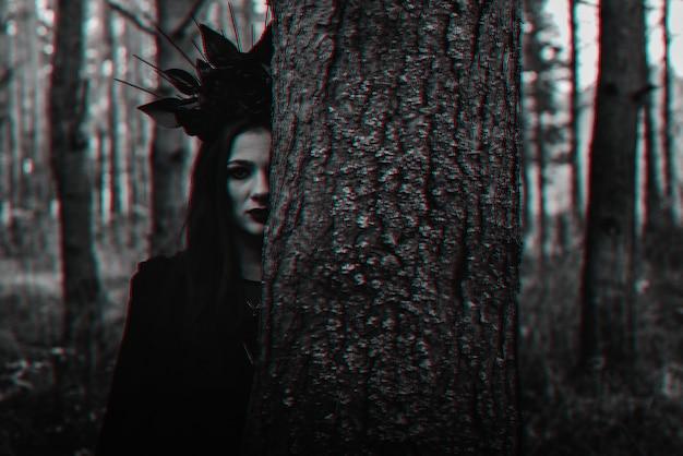 Темный портрет ведьмы в черном костюме в лесу. черно-белый с эффектом виртуальной реальности 3d глюк