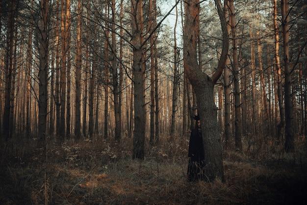 숲에서 검은 의상을 입은 마녀 소녀의 어두운 초상화